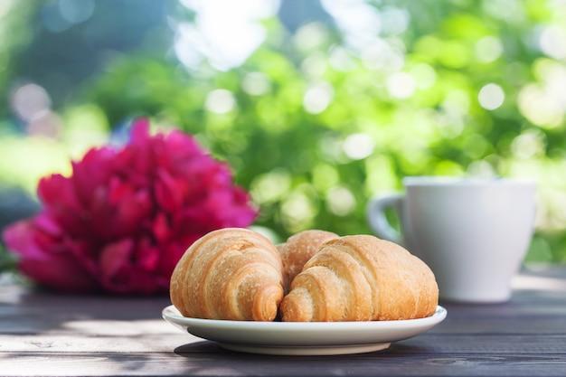 焼きたてのクロワッサンと庭のテーブルの上のコーヒーカップで朝食します。