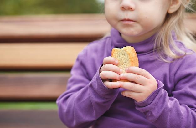 Маленькая девочка ест гренки