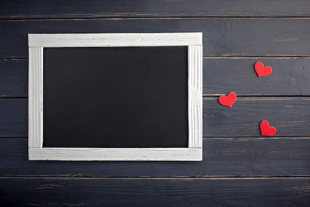 День святого валентина концепция с красными сердцами и доске на фоне дерева