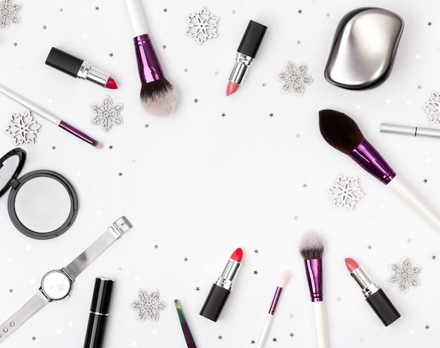 白いテーブルの上のクリスマスの装飾と女性のアクセサリー、化粧品、化粧道具