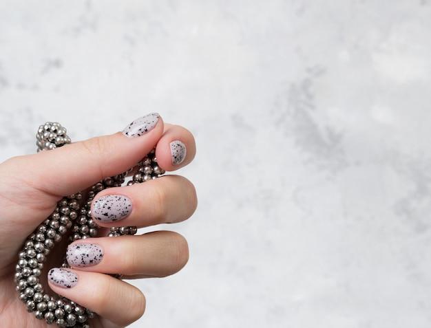 Руки молодой взрослой женщины с розовыми обнаженными модными ногтями на сером бетонном столе