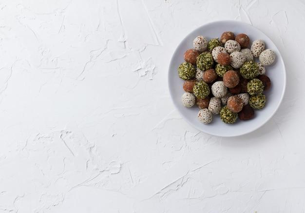 Укусы органической энергии с финиками, тыквенными семечками, миндалем, грецким орехом и кунжутом на белом столе.