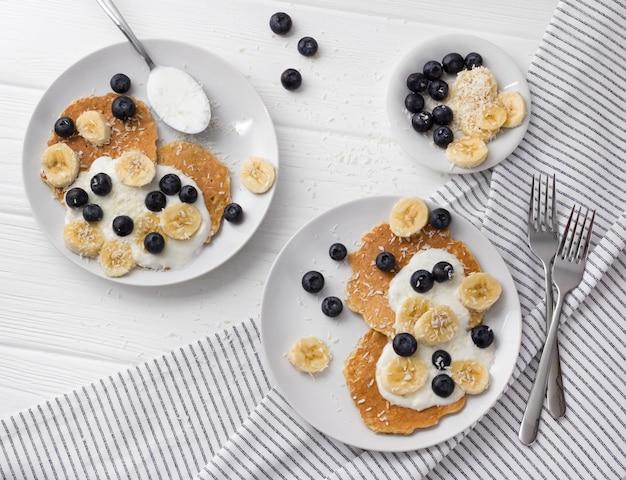 ヨーグルト、新鮮なブルーベリー、白い木製のテーブルでバナナの自家製オートミールパンケーキ。