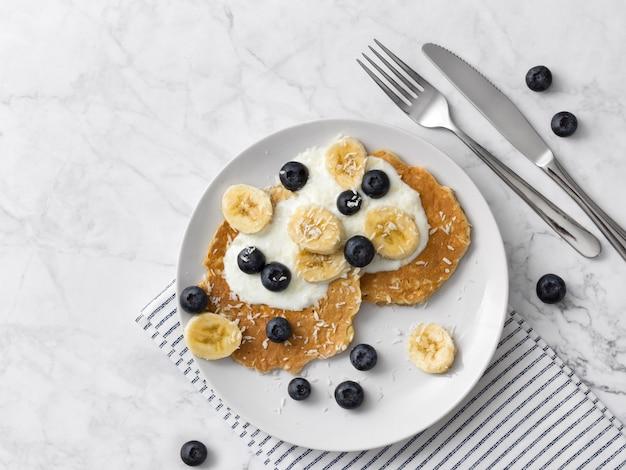 新鮮なベリー、フルーツ、ヨーグルトと健康的なパンケーキ。夏の朝食のコンセプトです。