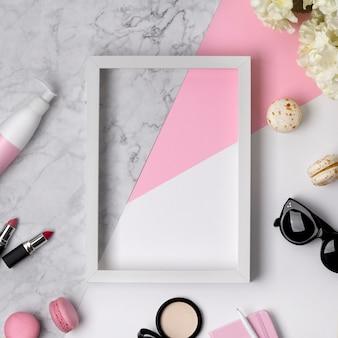 ピンク、大理石、白のパステルテーブルのフレーム、アクセサリー、装飾的な化粧品、花、お菓子の女性の美容デスクの平面図です。