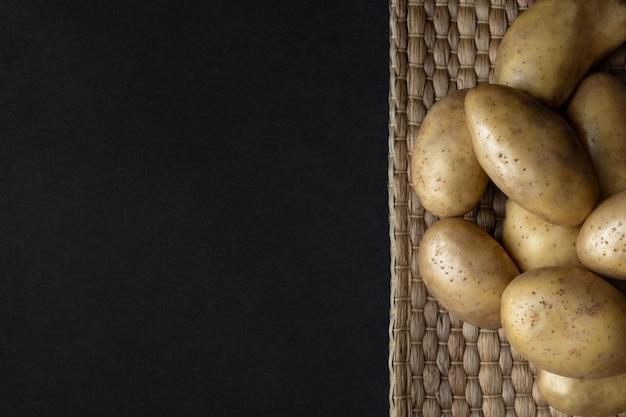 Куча сырого органического картофеля на соломенной салфетке на темном фоне