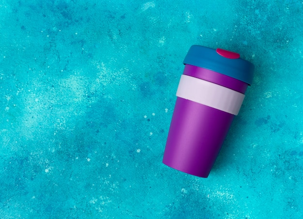 背景色が水色に再利用可能なコーヒーまたは紅茶のカラフルなカップマグカップ