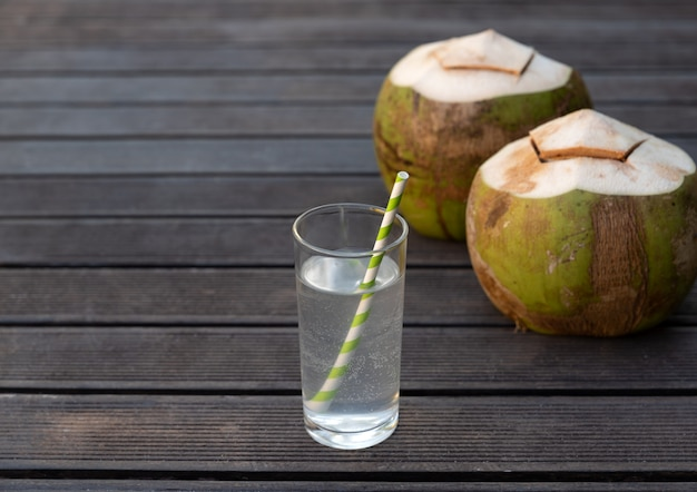 木製の背景にあるガラスの熱帯の新鮮なココナッツ水