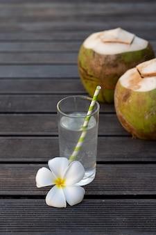 ガラスで熱帯の新鮮なココナッツ水装飾木製の背景にプルメリア