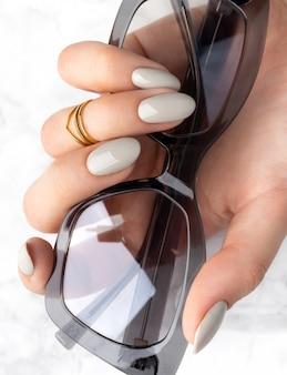 Красивая женская рука с маникюром держит солнцезащитные очки