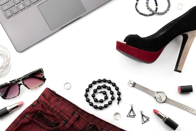 靴、スカート、白で隔離されるアクセサリーとラップトップ