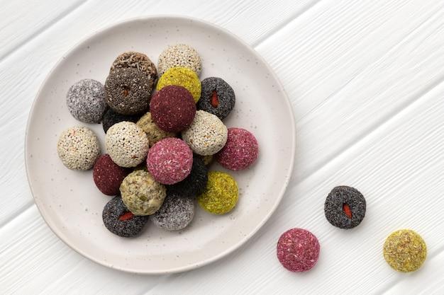 Красочные веганские конфеты энергетические шарики на тарелку на белом деревянном столе