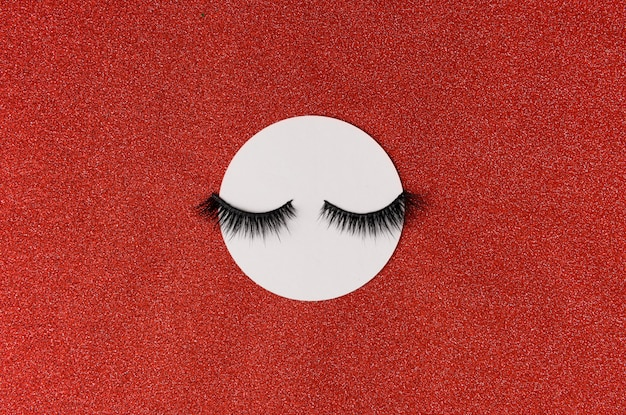 Креативный макет с ресницами. закрытые глаза на красном фоне сверкающих
