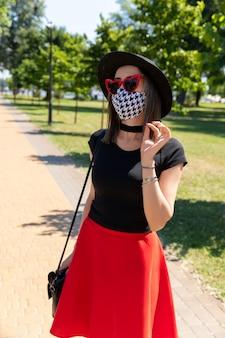 公園を歩いている防護マスクで美しい女性のファッションの肖像画。トレンディな服のメガネアクセサリー。新しい通常のコンセプト
