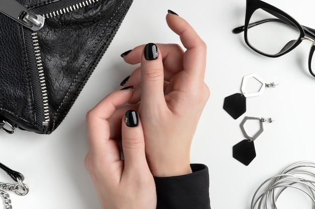 エレガントなマニキュアで美しい女性の手。最小限のブラックネイルデザイン。