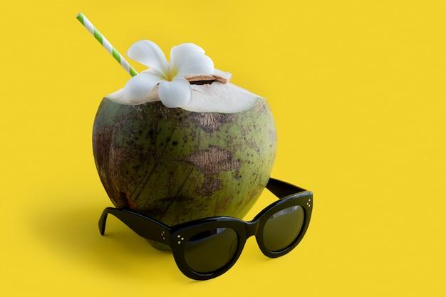 黄色の背景にサングラスをかけた熱帯の新鮮なココナッツカクテルの装飾が施されたプルメリア。