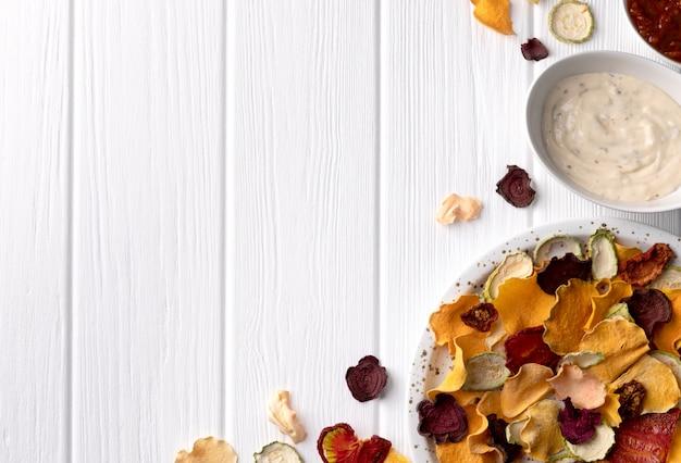 カリカリカリカリ有機野菜チップ、オーブン焼きカボチャ、ビートルート、トマト、にんじんチップスナック添え、白い木製のテーブル