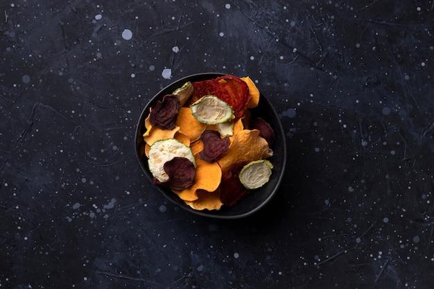 オーブンで焼いたカボチャ、ビートルート、スカッシュ、トマト、にんじんチップスナックが入ったカリカリの有機野菜チップ