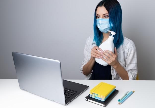 ホームオフィスに座っているラップトップのコンテンツを探している防護マスクの青い髪の心配している女性