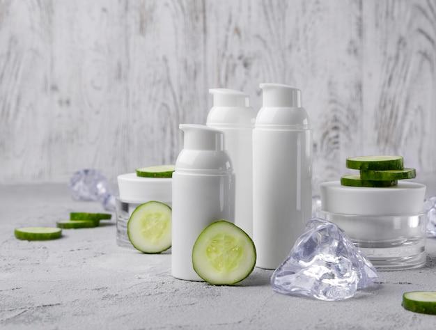 キュウリと灰色のテーブルの上の氷の化粧品クリームボトルのセット。