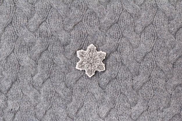 Текстура серого трикотажа крупным планом с деревянной снежинкой