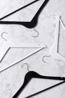 シンプルなトップビューフラットは、大理石のテーブルに黒と白の木製ハンガーを置く