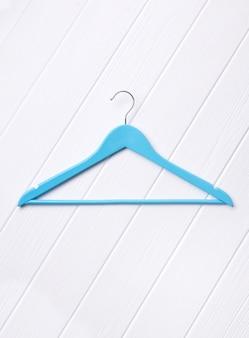 トップビューフラットは、木製のテーブルで単一の青い木製ハンガーを置きます。