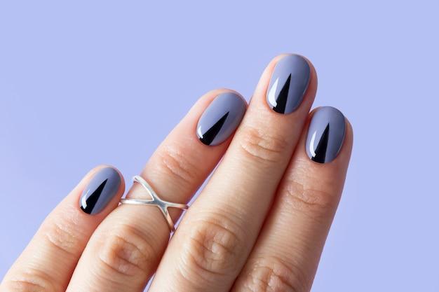 幾何学的な最小限のマニキュアで美しい女性の爪