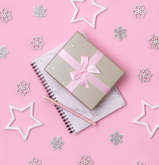 クリスマス冬のお祝いのコンセプト。ペンとピンクの背景のギフトと大理石のメモ帳