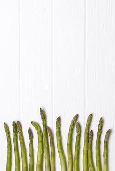 Куча свежей зеленой спаржи на белом столе деревянный стол.