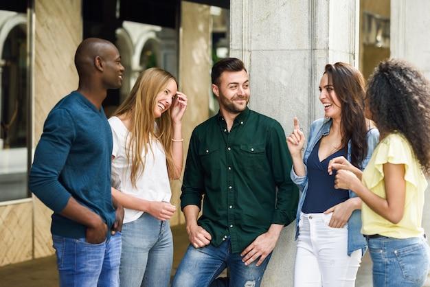 都市の背中で一緒に楽しむ友人の多民族グループ