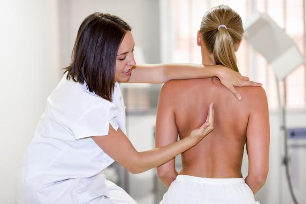 Медицинский осмотр у плеча в физиотерапевтическом центре.
