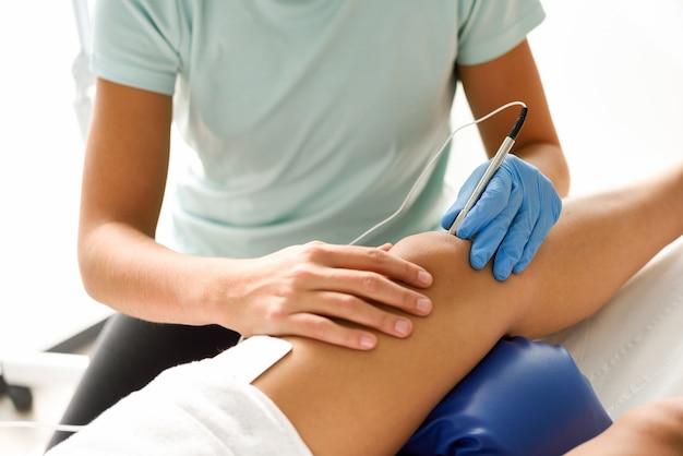 女性の膝の針で静電鍼治療
