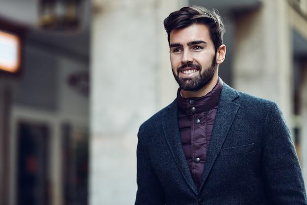 Молодой бородатый улыбающийся человек в британском элегантном костюме на улице.