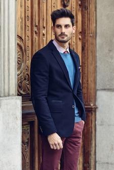 Привлекательный мужчина носить британский элегантный костюм на улице. современная прическа.