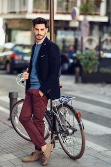 Человек в британском элегантном костюме на улице возле старого велосипеда