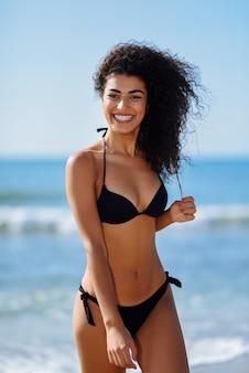 トロピカルビーチで笑いを浮かべて水着で美しい体と若いアラビア人の女性。
