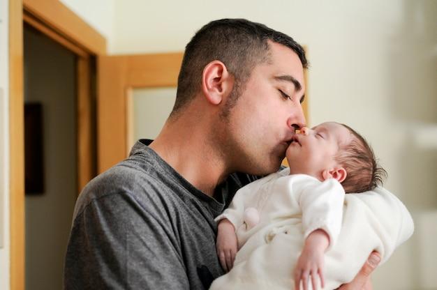 彼の新生児の女の子にキスする父。