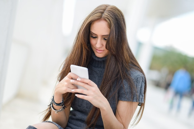 Длинношерстные девушка текстовых сообщений на своем мобильном телефоне