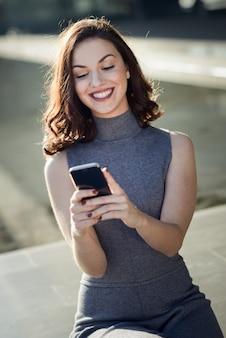 Очаровательная женщина с смартфон в солнечный день