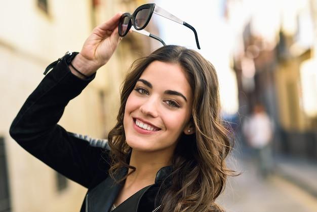 長い髪は彼女のサングラスを持った女性のクローズアップ