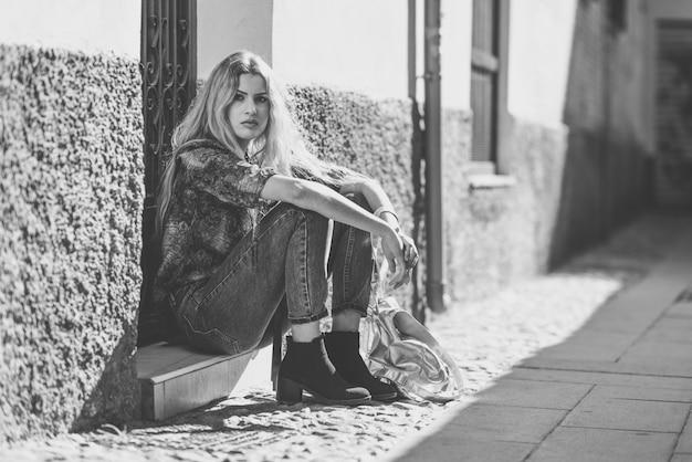 Женщина, сидящая на ступеньку двери