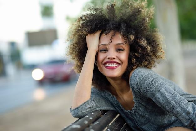 女性は木のベンチの後ろに彼女の頭でポーズ笑顔