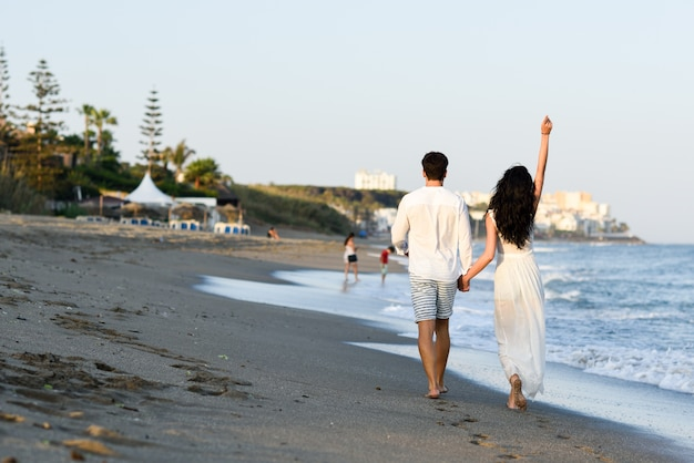 Мужчина и женщина, идущая рука об руку на пляже