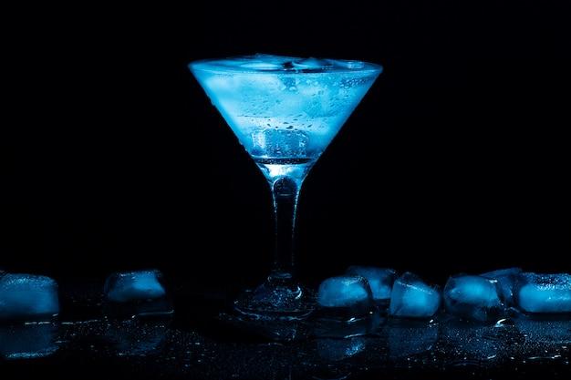 黒いテーブルの上のグラスに氷とカクテルマティーニ