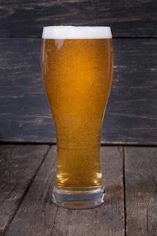 暗い木製のテーブルの上のガラスのラガードラフトビール