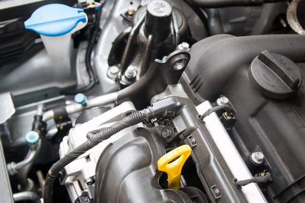車のエンジンのクローズアップの要素。オイルゲージ、ワイヤー、ウォッシャー液リザーバー