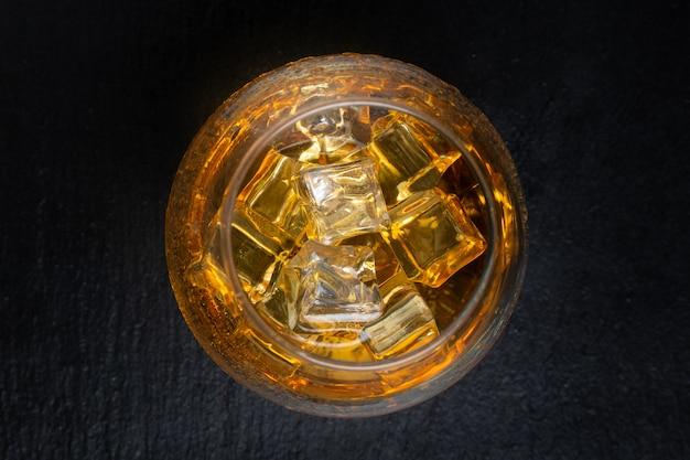 ウイスキーと黒いテーブルの上の氷とガラス。上面図。