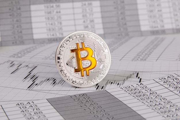 Биткойн-монета на финансовых чатах и графике