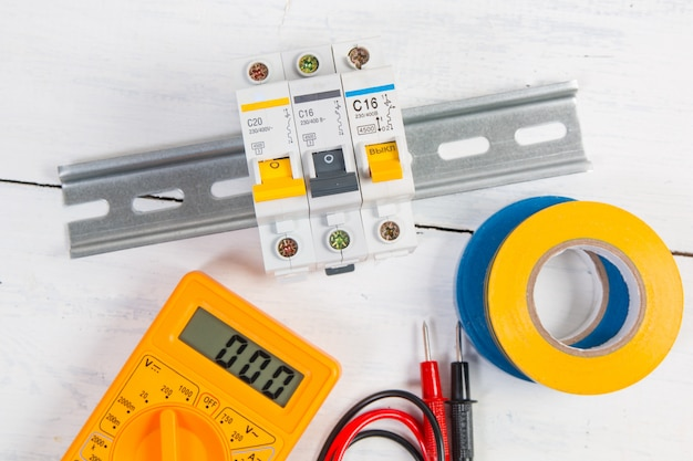 電気モジュラーサーキットブレーカー、絶縁テープ、デジタルマルチメーター。電気ネットワークの保護と切り替え。